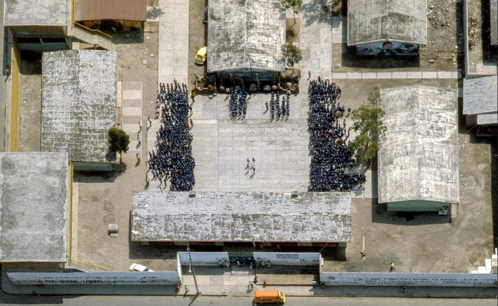 Una toma aérea en la que se aprecia una escuela de la delegación Iztapalapa en el momento justo en que todos los alumnos de nivel secundaria se reúnen en el patio para realizar los honores a la bandera. La fotografía fue tomada en 1985. Cortesía: Bob Scha