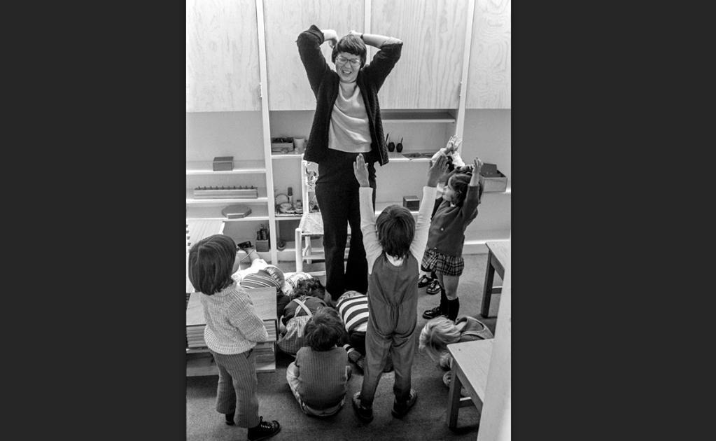 Una fotografía que capta la magia del momento en que los niños aprenden jugando. Mientras unos pequeños siguen las instrucciones y permanecen agachados, otros imitan los movimientos de la maestra durante una clase en un colegio Montessori, por el rumbo de