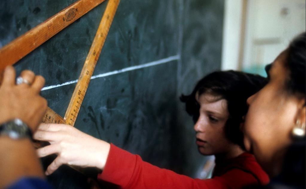 La maestra hace uso de una escuadra de madera para guiar los trazos de la joven estudiante en el pizarrón para que ella pueda hacer lo mismo en su cuaderno de dibujo. El correcto manejo de la regla y las escuadras, con aquellos enormes instrumentos geomét