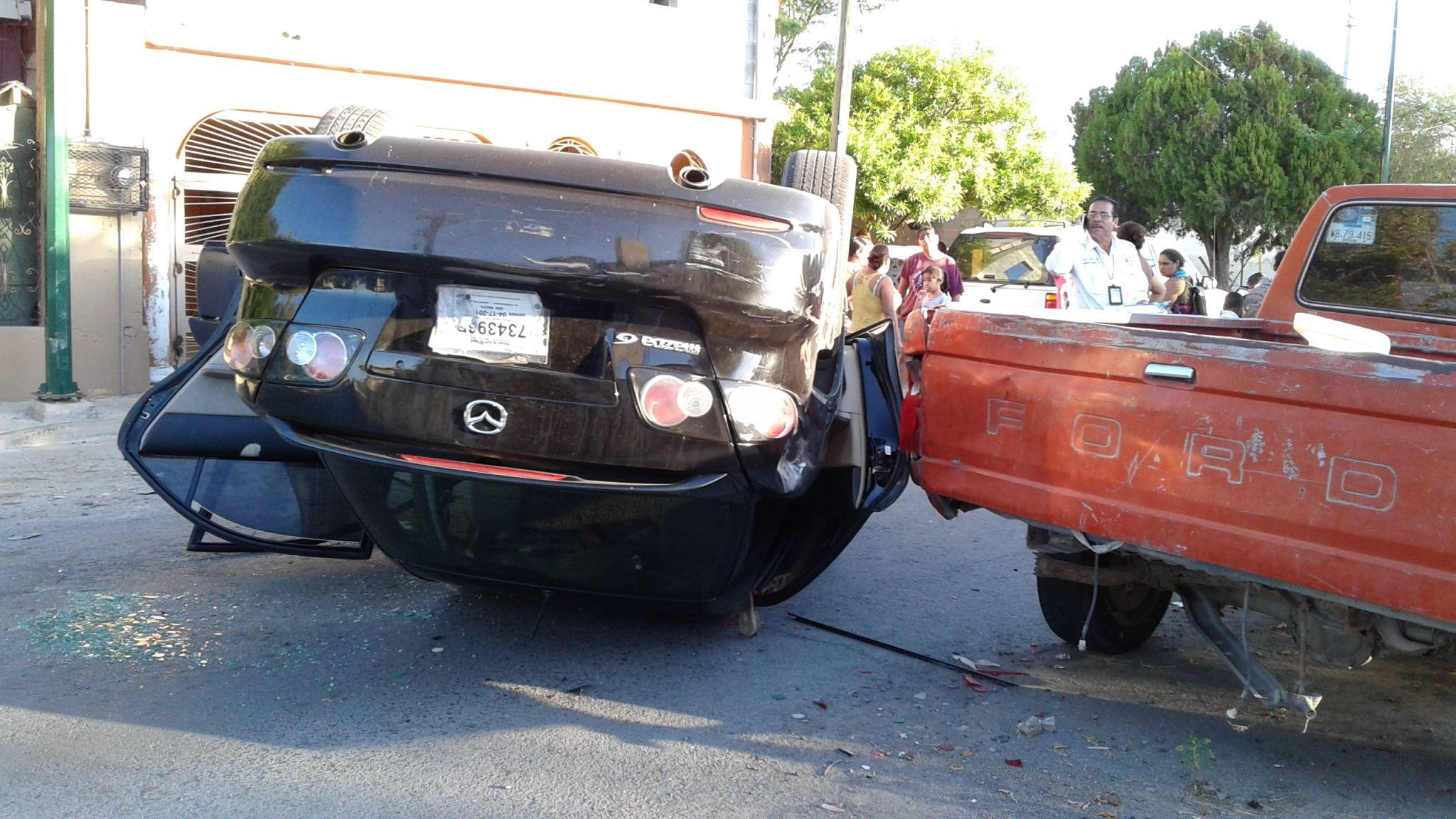VOLCADO. El automóvil sedán, marca Mazda 6, terminó volcado sobre la calle Río San Fernando del fraccionamiento Río Bravo, tras haberse impactado contra un par de camionetas estacionadas.(foto: Heriberto Rodríguez)