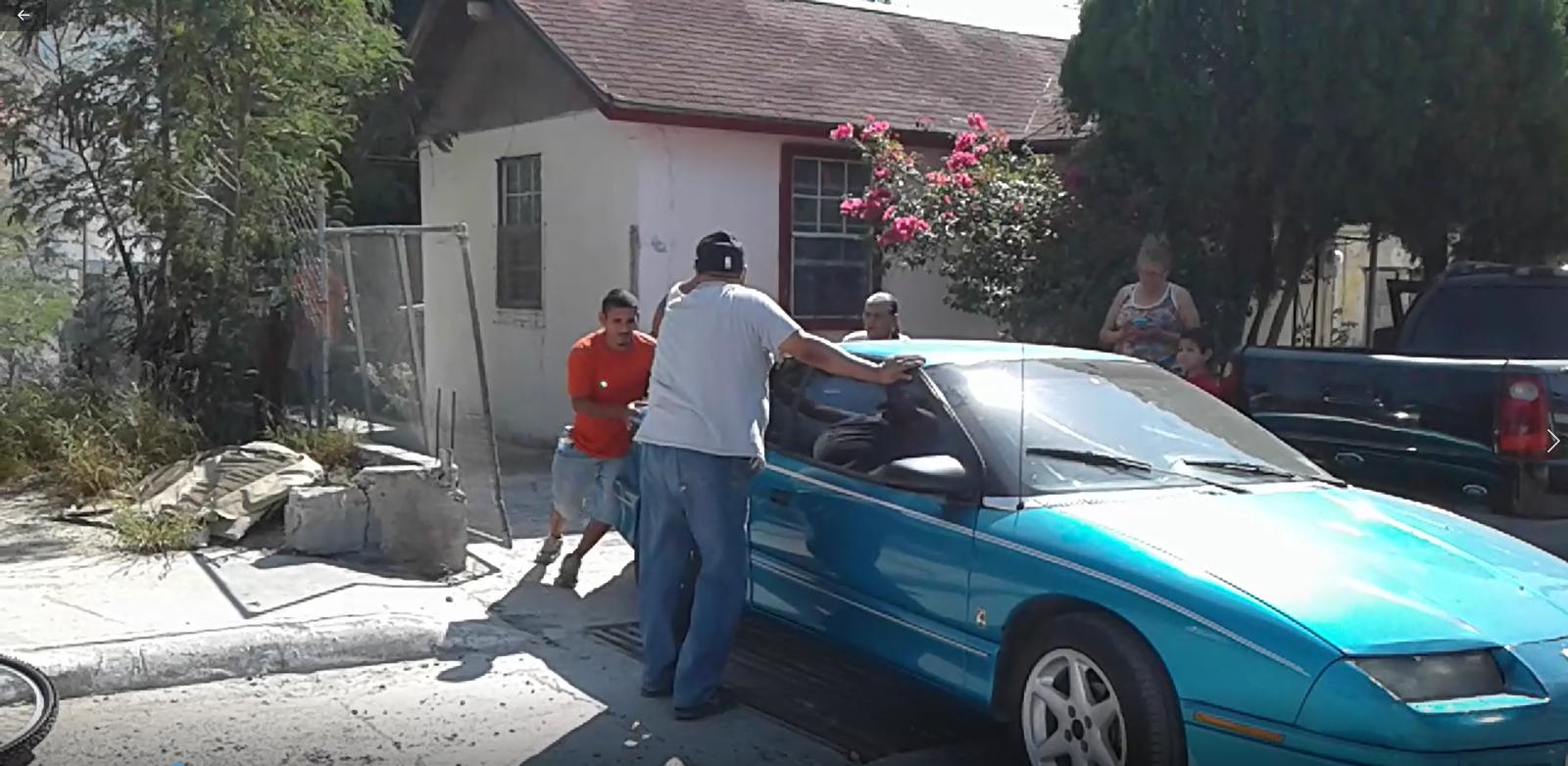 """EXTRAEN. Vecinos de la avenida Manuel Hinojosa, tuvieron que extraer de los patios de sus viviendas varios autos que podían ser alcanzados por el fuego que se originó en el Arroyo """"El Buey""""."""