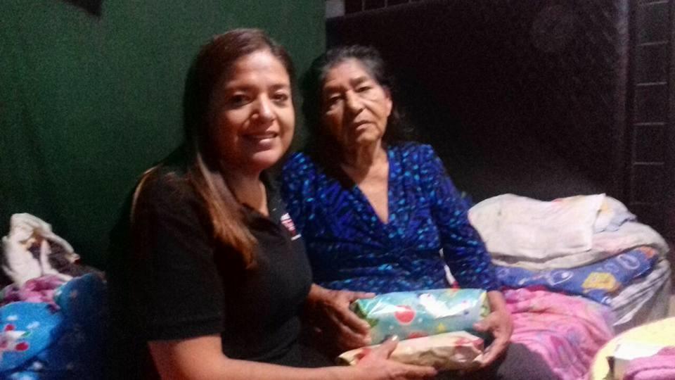REPARTE. La pastora Norma Robledoacudió hasta el domicilio de una abuelita que tampoco pudo asistir al festejo navideño, por lo que le llevó algunos regalitos.