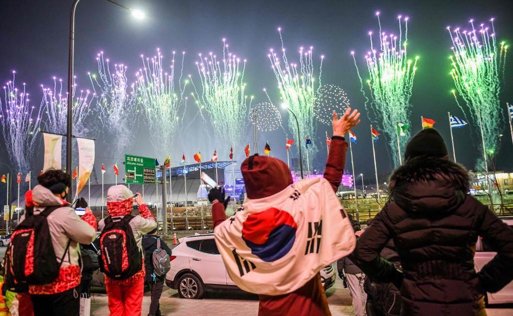La gente con una bandera de Corea del Sur mirando los fuegos artificiales fuera del estadio durante la ceremonia de inauguración de los Juegos Olímpicos de Invierno Pyeongchang 2018 (Foto: AFP)