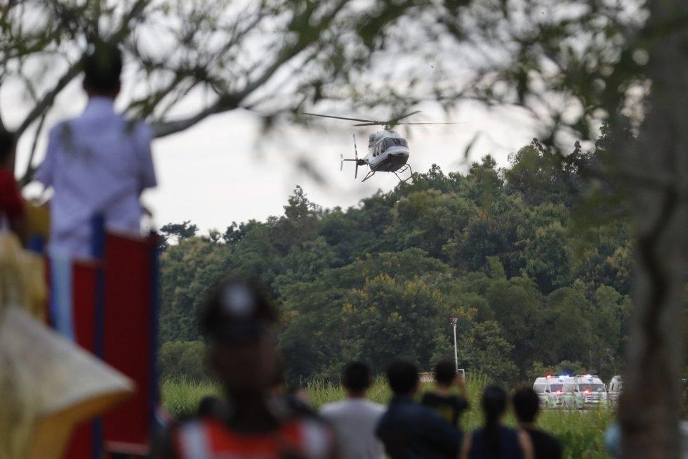 Ciudadanos observan un helicóptero que supuestamente traslada a uno de los niños rescatados de la cueva de Tham Luang (Tailandia) hacia el hospital, el 10 de julio de 2018.