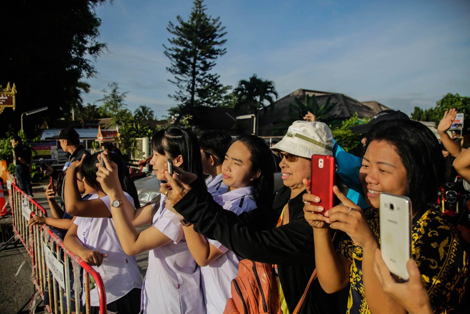 Varios ciudadanos de Tailandiahacen fotografías con sus móviles del helicóptero que ha trasladado al quinto niño rescatado tras salir de la cueva, el 9 de julio de 2018.