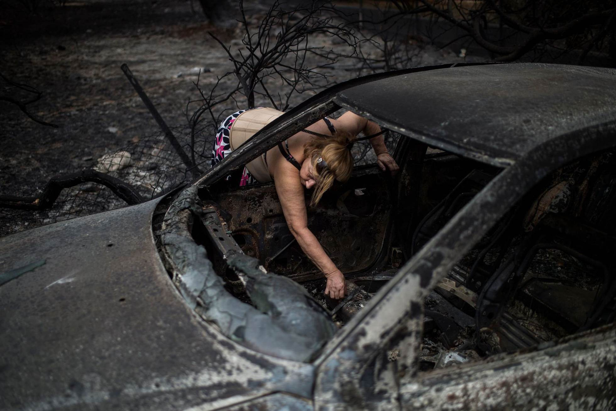 Una mujer coge papeles en el interior de su vehículo calcinado tras el incendio forestal en la ciudad griega de Mati.