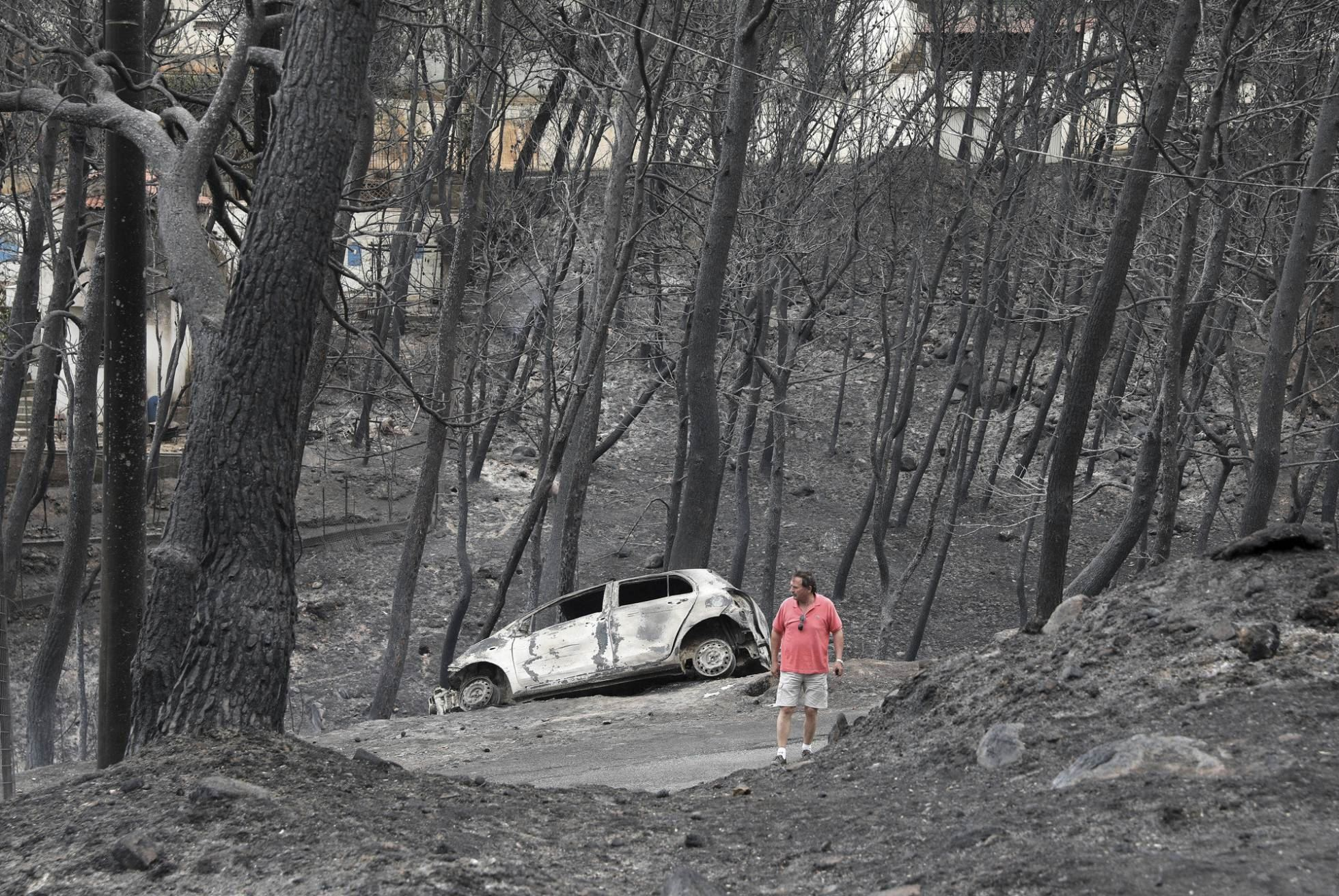 Un hombre pasa junto a un vehículo calcinado en el pueblo de Neos Voutzas, cerca de Atenas.
