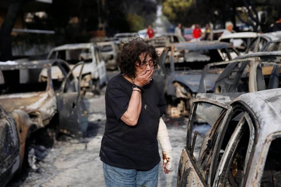 Una mujer llora mientras intenta encontrar a su perro, perdido durante el incendio en Mati (Grecia).