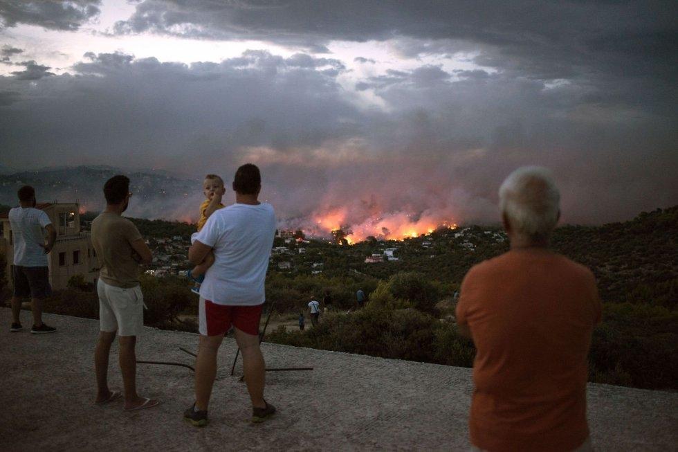 Un grupo de vecinos observa el incendio incontrolado en la ciudad de Rafina (Grecia).