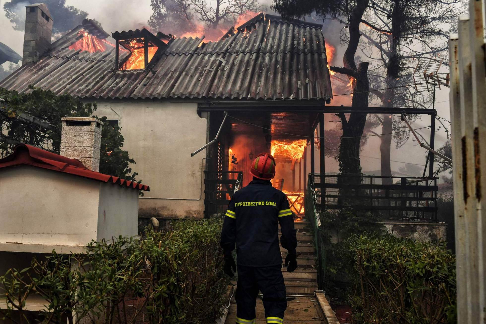 Un bombero junto a una casa incendiada en Kineta (Grecia).