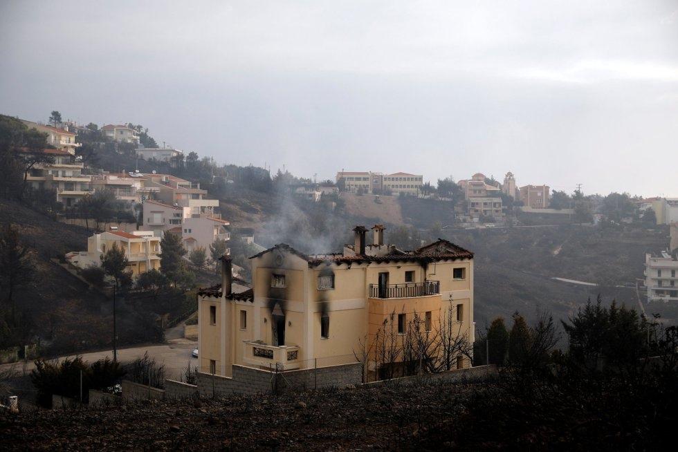 Una casa continúa echando humo tras el paso del incendio por Neos Voutzas (Grecia).