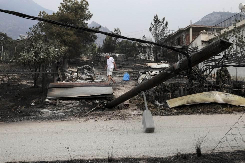 Un hombre busca pertenencias que pueda recuperar entre los restos calcinados de su casa en Kineta (Grecia).