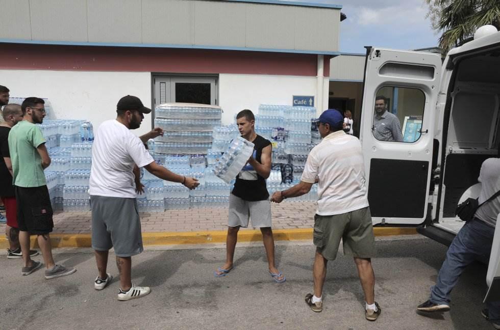 Varias personas meten botellas de agua en una furgoneta para sumistrar a las personas rescatadas del incendio forestal en Nea Makri, Atenas.