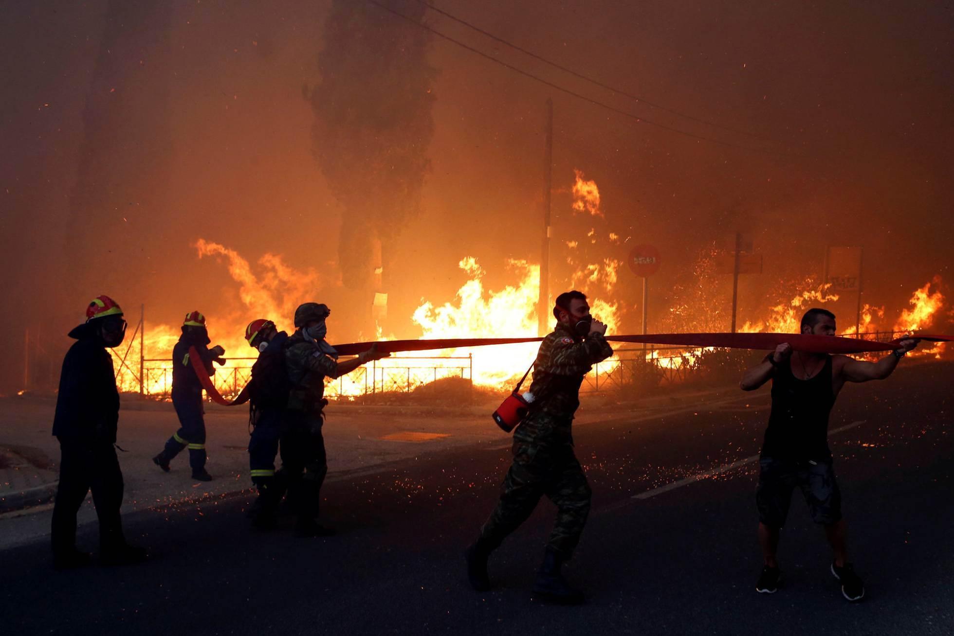 Bomberos y voluntarios intentan apagar las llamas en Rafina (Grecia).