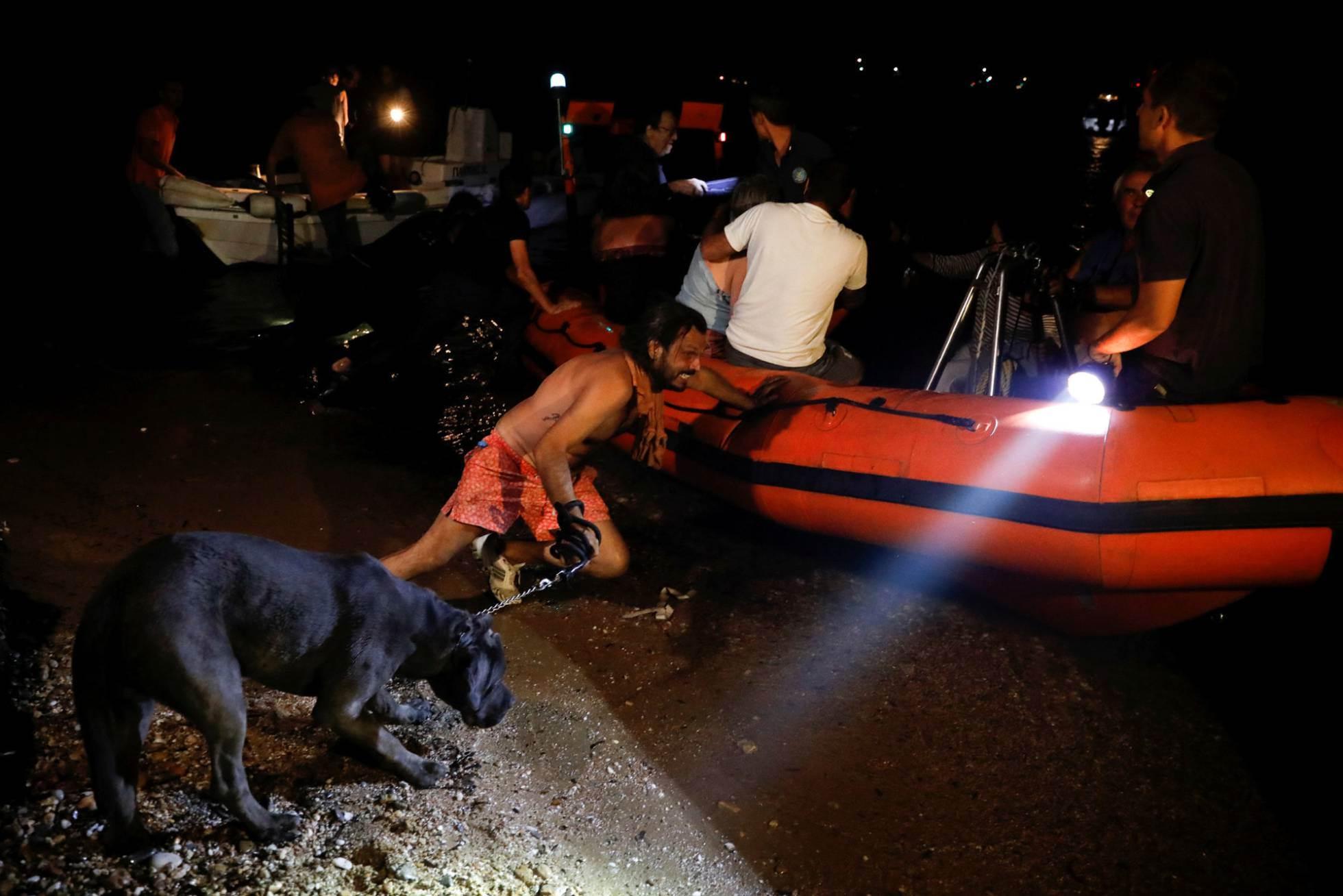 Un hombre, junto a su perro, empuja un bote salvavidas durante la evacuación de vecinos en el pueblo costero de Mati (Grecia).