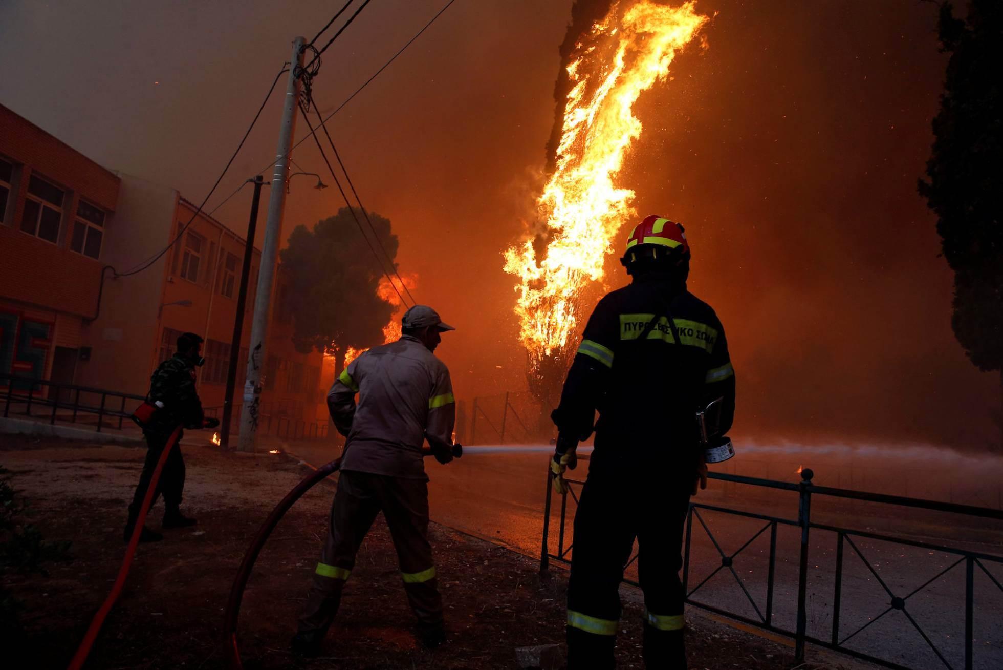 Las tareas de extinción continuaron durante toda la noche pero se vieron dificultadas por los fuertes vientos que alcanzaron fuerza siete en la escala de Beaufort. En la imagen, bomberos intentan apagar las llamas en el pueblo de Rafina (Grecia).