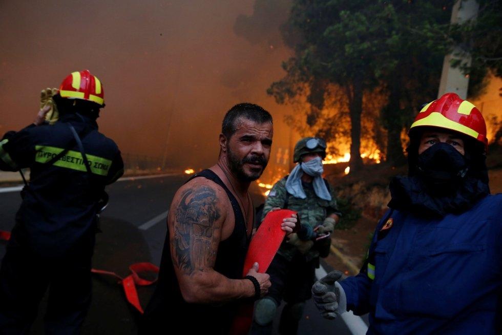 Las autoridades portuarias, indicaron a la AFP que habían hallado cuatro cuerpos en el mar, los de tres mujeres y un niño, fallecidos cuando intentaban protegerse de las llamas. En la imagen, bomberos intentan apagar las llamas en Rafina (Grecia).