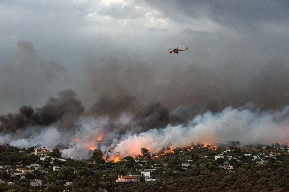 En Grecia, la mayoría de las víctimas quedaron atrapadas en el sector de la localidad balnearia de Mati, unos 40 km al noreste de Atenas. En la imagen, u n helicóptero sobrevuela el pueblo de Rafina, rodeado por las llamas.