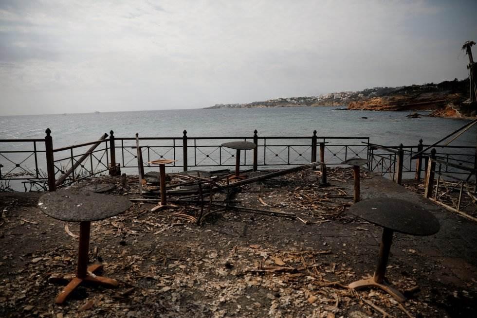 Mesas y sillas quemadas de un café junto al mar en la aldea de Mati.