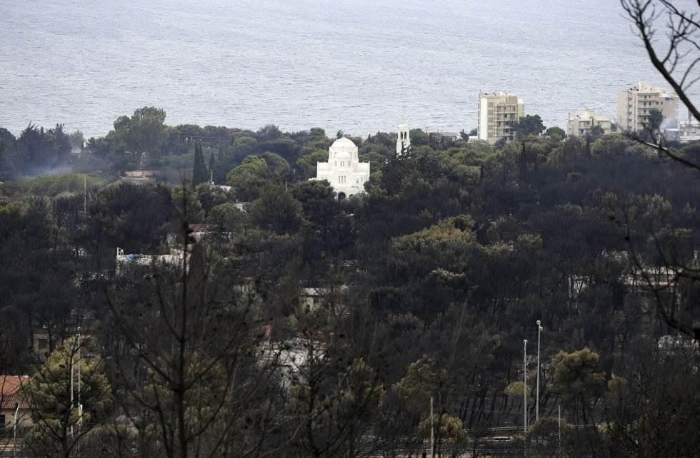 Una iglesia griega ortodoxa aparentemente intacta se destaca entre los árboles en el pueblo de Neos Voutzas, cerca de Atenas.