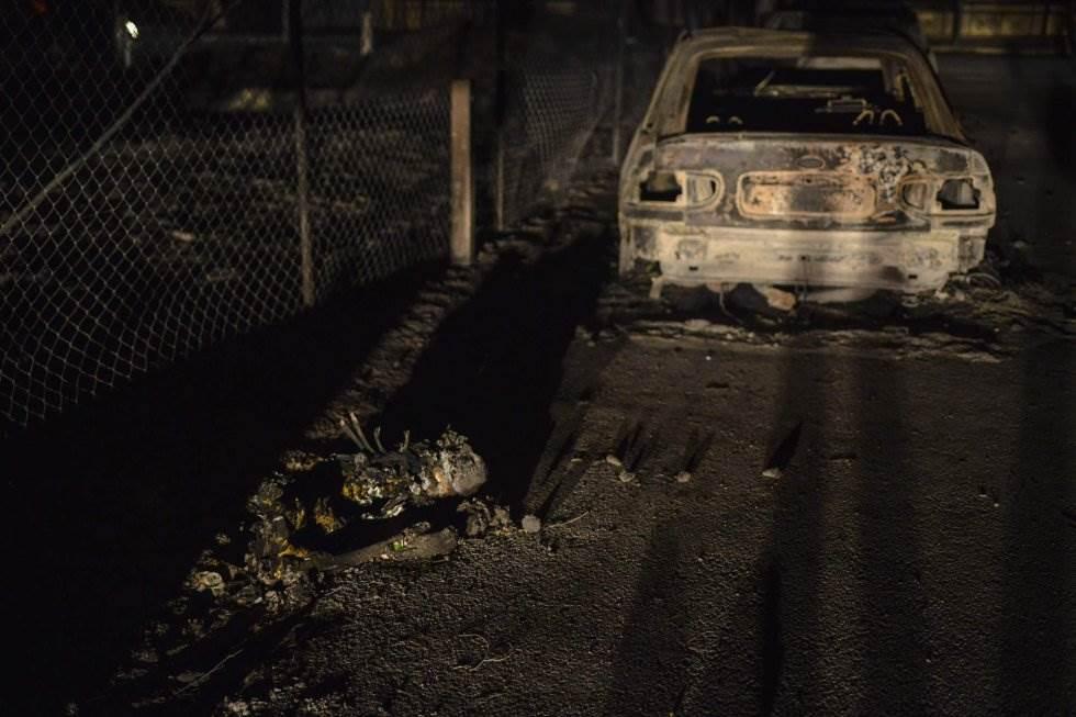 Un cuerpo carbonizado junto a un automóvil calcinado durante los incendios forestales en la aldea de Mati, cerca de Atenas.