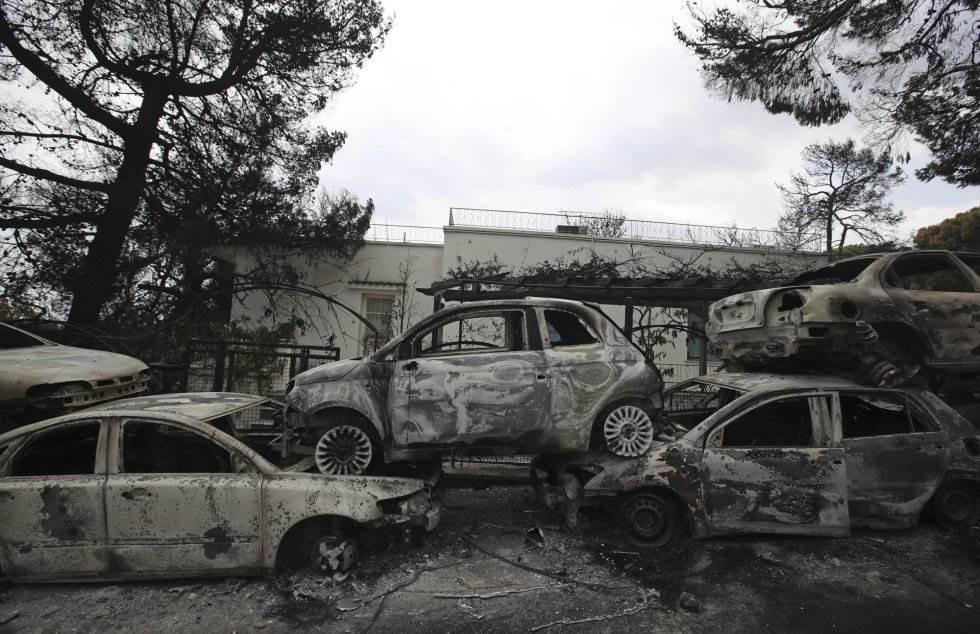 Los coches calcinados se amontonan a lo largo de una carretera en Mati, al este de Atenas (Grecia).