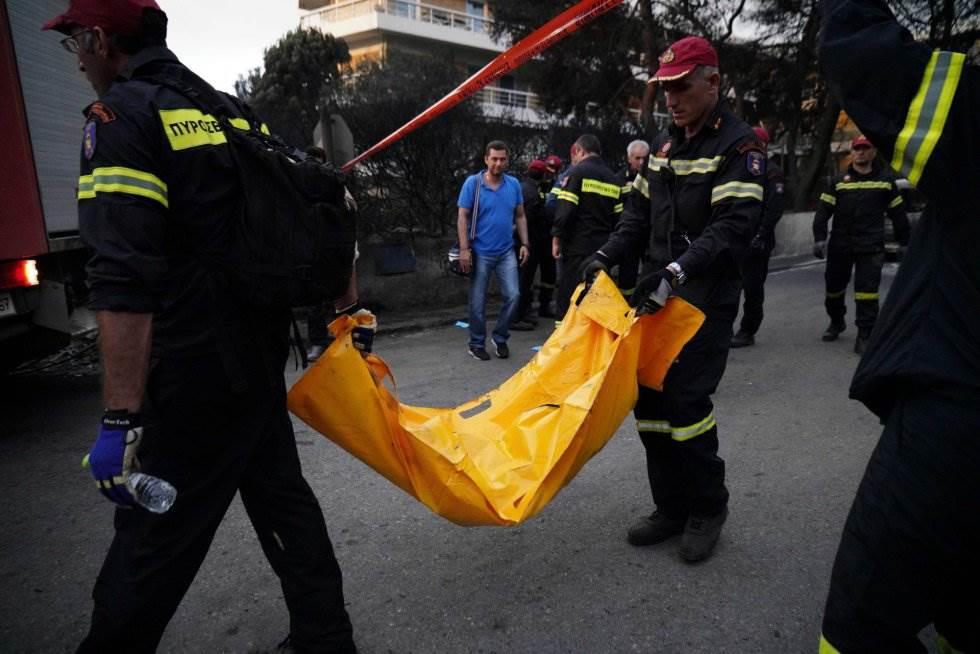 Los bomberos trasladan el cuerpo sin vida de una persona tras el incendio forestal en la aldea de Mati, cerca de Atenas. La cifra de muertos asciende a 70 personas.