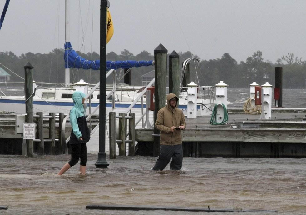 Jamie Thompson y Ryan Thompson caminan a través sobre una zona inundadas a lo largo del río Neuse en New Bern (Carolina del Norte). GRAY WHITLEY AP