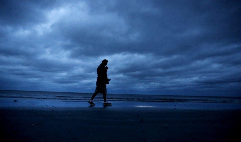 Russ Lewis busca camina a lo largo de a playa durante el acercamiento del huracán Florence a Myrtle Beach. DAVID GOLDMAN AP