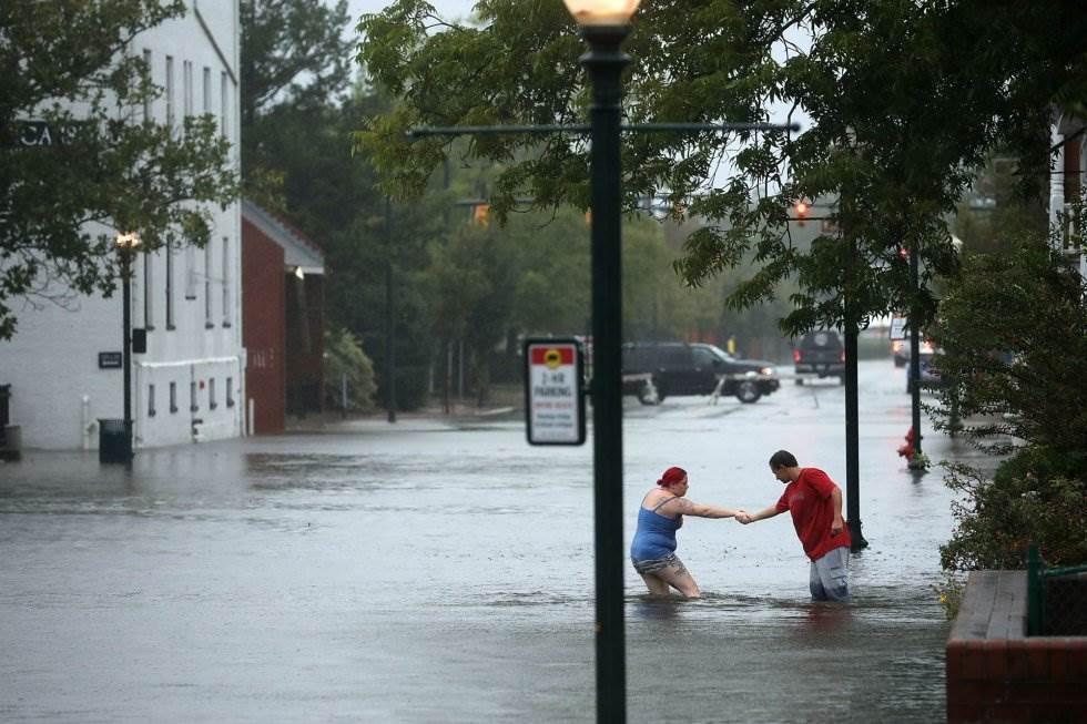 Dos vecinos cruzan una calle inundada de una zona residencial de New Bern (Carolina del Norte), el 13 de septiembre. CHIP SOMODEVILLA AFP