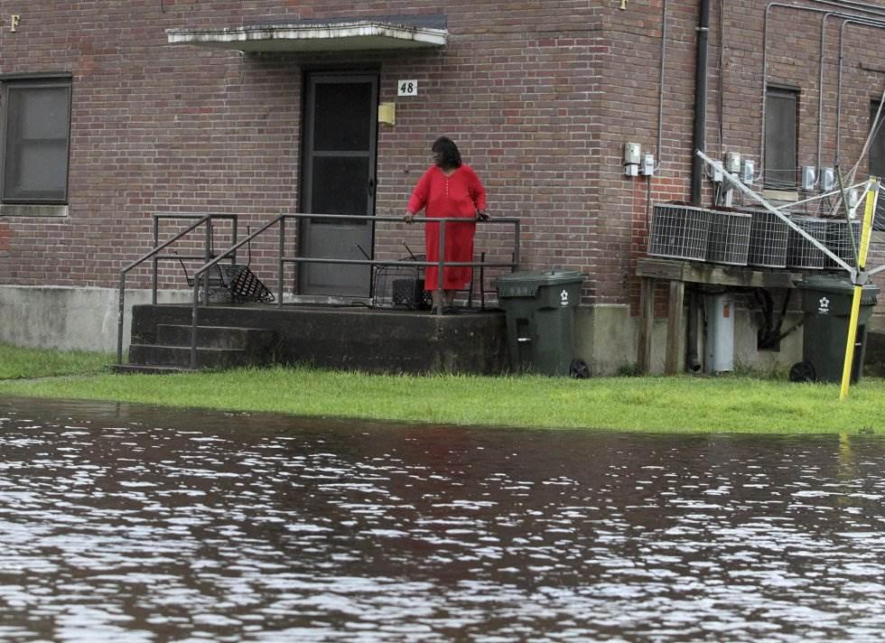 Una vecina observa desde el portal del su edificio la calle inundada en New Bern (Carolina del Norte). GRAY WHITLEY AP