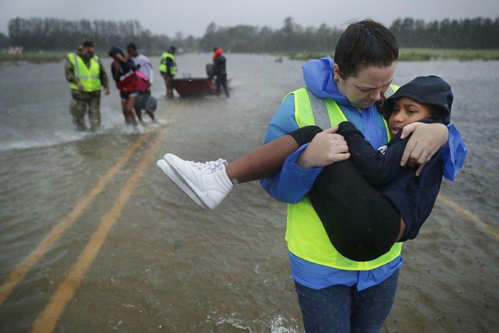 Voluntarios del Equipo Civil de Respuesta a Crisis ayudan a rescatar a tres niños de un hogar inundado en James City. CHIP SOMODEVILLA AFP