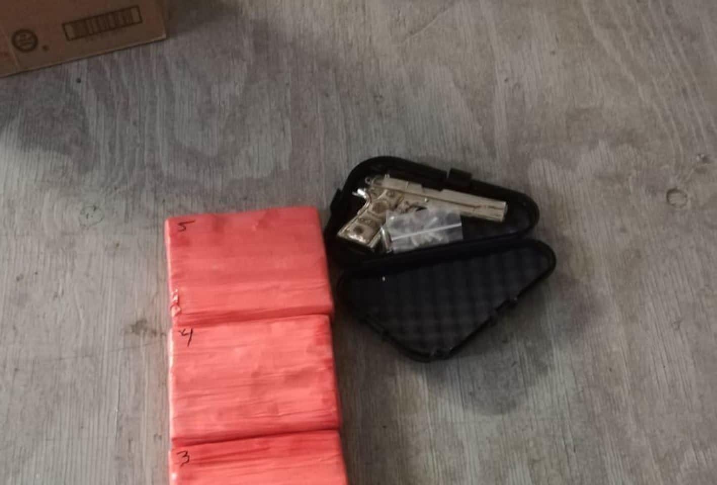 ARMA. La pistola y paquetes conteniendo mariguana hallados en el operativo.