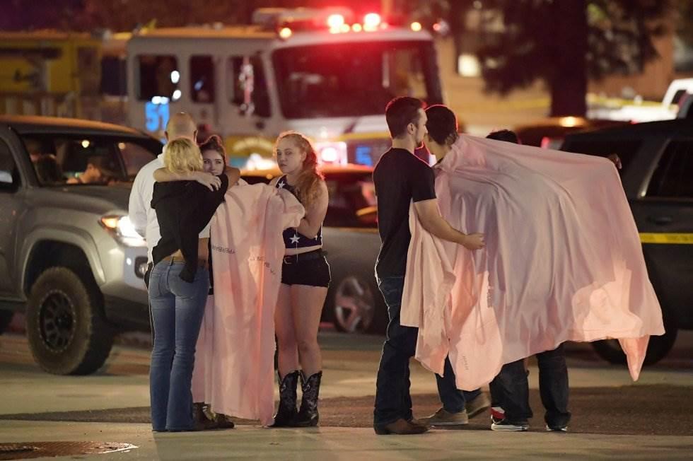 11 Un grupo de jóvenes se protege del frío, en las proximidades de la zona del tiroteo, en Thousand Oaks (California).