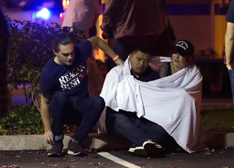14 Un grupo de jóvenes se consuelan, sentados en las proximidades del tiroteo que ha tenido lugar en Thousand Oaks, Los Ángeles.