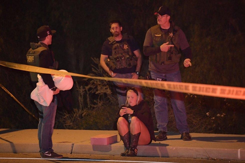 19 Agentes de policía conversan al lado de una testigo del tiroteo del bar Borderline, en las afueras de Los Ángeles.