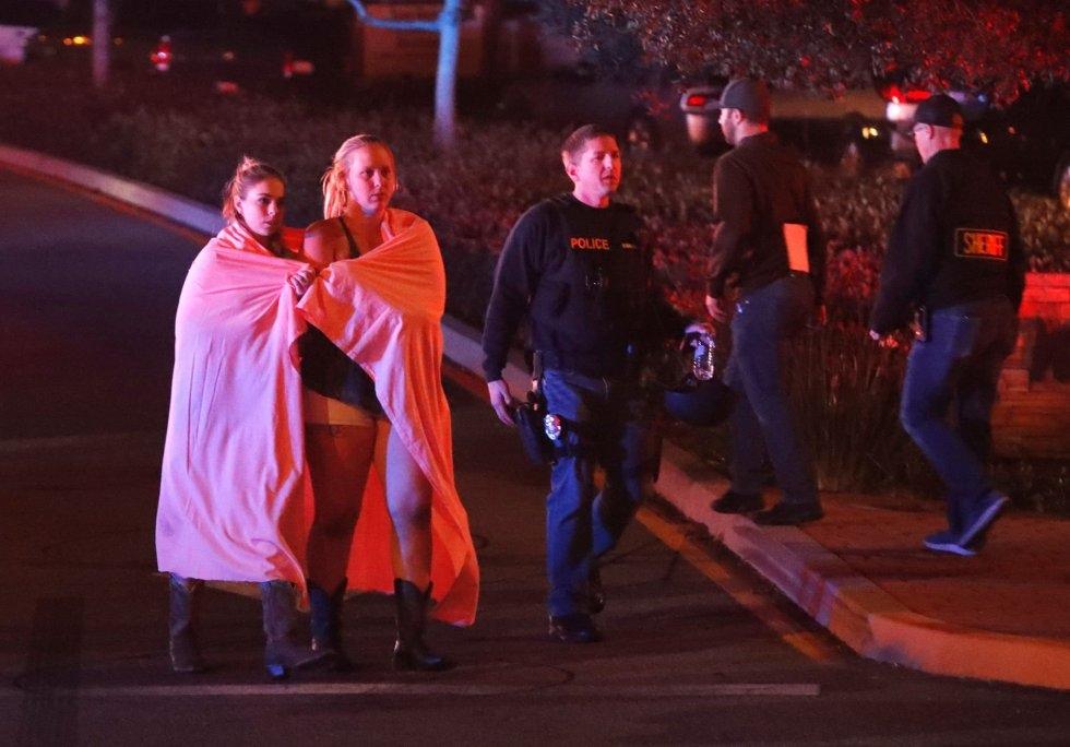 1 Dos mujeres envueltas en una sábana abandonan el área del tiroteo cerca del bar Borderline, en Thousand Oaks, un suburbio en las afueras de Los Ángeles (California).