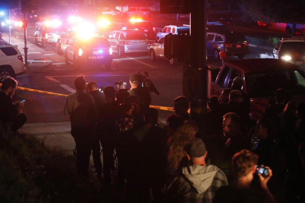 21 Un grupo de personas y varios periodistas esperan junto al cordón policial tras el tiroteo en el bar Borderline, en Thousand Oaks, a las afueras de Los Ángeles.