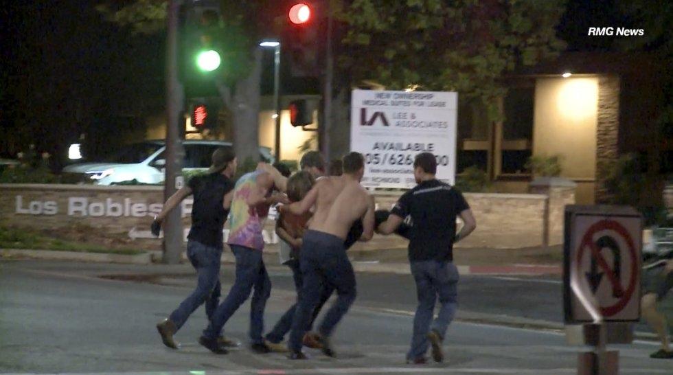 8 Un grupo de personas ayuda a una de las víctimas heridas en el tiroteo en Thousand Oaks, un suburbio en las afueras de Los Ángeles (California).