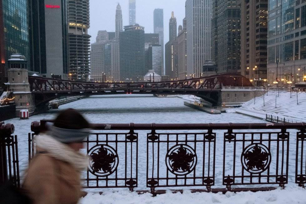 Una mujer atraviesa un puente sobre el río Chicago.