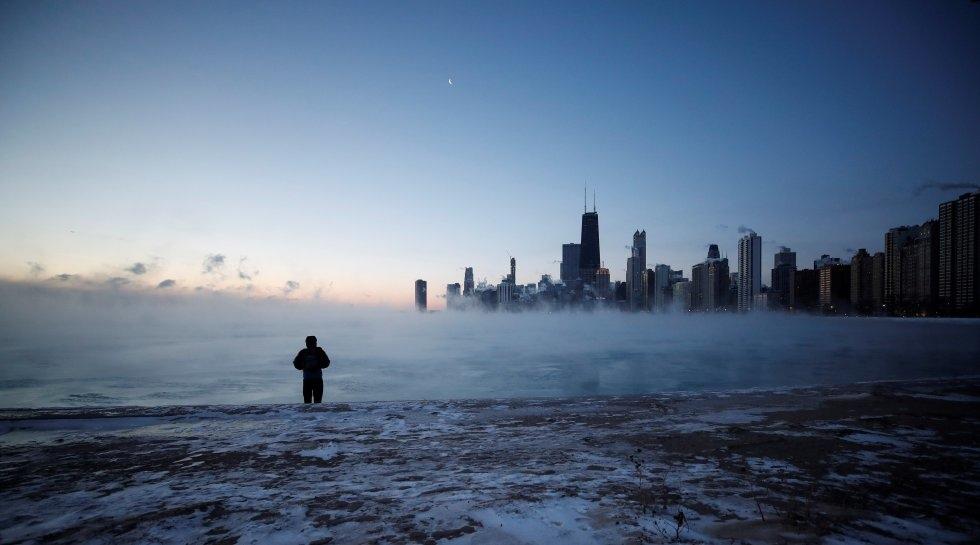 Un hombre camina por la playa de la Avenida Norte al amanecer de este miércoles en el lago Michigan en Chicago( Estados Unidos).