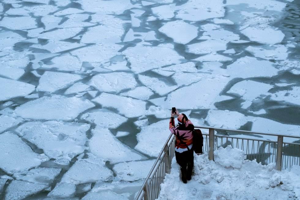 Una mujer hace una foto con su móvil al río Chicago, parcialmente congelado, este martes.