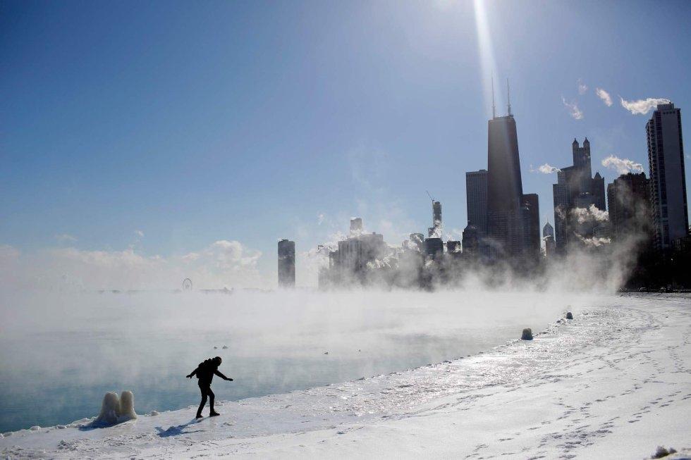 Una mujer camina cerca del lago Míchigan helado con Chicago al fondo, el 30 de enero de 2019.