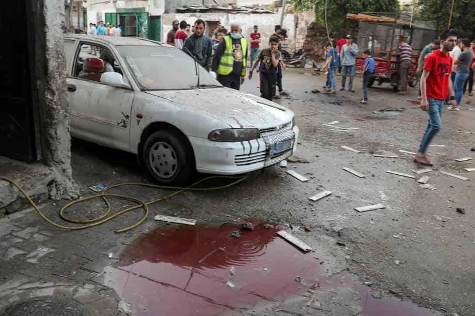 Varias personas observan en lugar en el que murieron varios palestinos tras un ataque israelí, en el norte de la franja de Gaza. MOHAMMED SALEM REUTERS